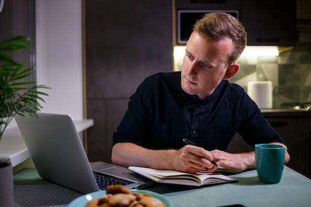 Uomo d'affari di successo seduto a un tavolo a casa, guardando lo schermo di un laptop, si sente soddisfatto con orgoglio per il lavoro svolto, l'uomo sereno lavora, le mani dietro la testa, lavora a casa