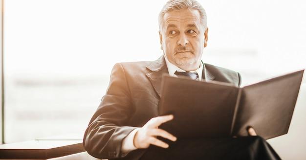 Imprenditore di successo studia documenti di lavoro seduto sul divano