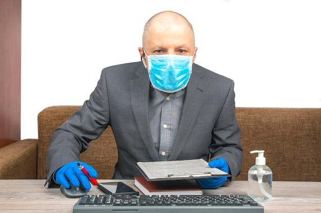 Un uomo d'affari di successo lavora in ufficio durante la quarantena del coronavirus. lavora come libero professionista online.