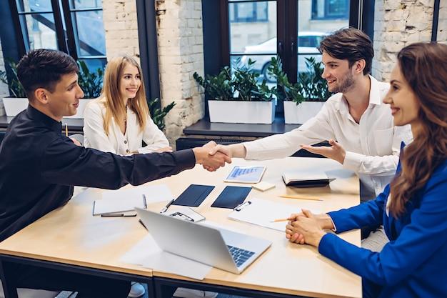 Imprenditori di successo che agitano le mani al tavolo in ufficio