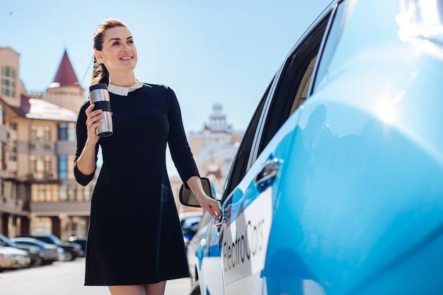 Imprenditrice di successo. felice piacevole donna attraente in piedi vicino alla sua auto e aprendola mentre si tiene una tazza termica