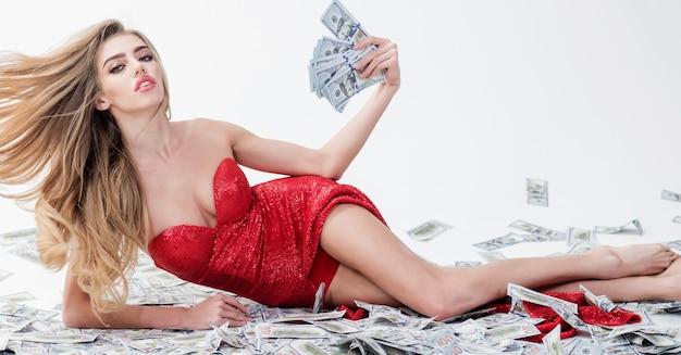 Imprenditrice di successo che si trova in banconote. la bella ragazza in vestito rosso elegante tiene i soldi a disposizione.