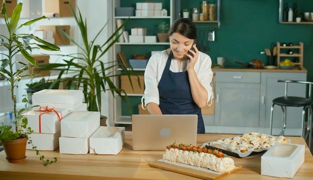 Una donna d'affari di successo che gestisce la sua attività lavora in una cucina accogliente con interni moderni, utilizzando un computer e un telefono cellulare. pasticciere, piccolo imprenditore. avviare.