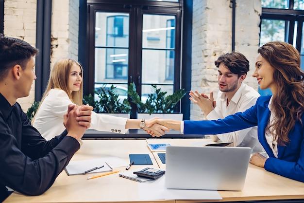 Imprenditrici di successo si stringono la mano mentre gli uomini d'affari battendo le mani al tavolo in ufficio