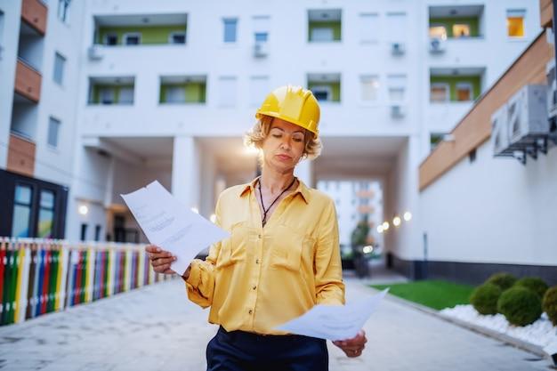 Architetto femminile senior caucasico riuscito con il casco sulla testa che esamina i documenti mentre levandosi in piedi all'aperto.