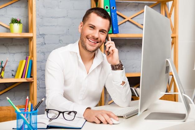 Gestore allegro di successo che parla al telefono con i suoi clienti