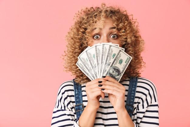 Donna riccia di successo 20s holding fan di soldi in dollari mentre si trovava