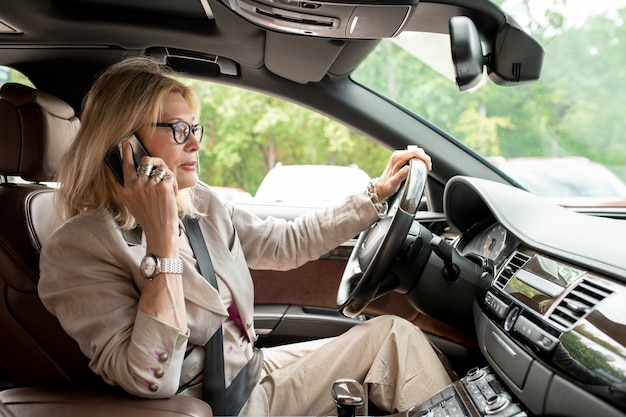 Elegante imprenditrice di successo che tiene al volante mentre è seduta in macchina, guida al lavoro e fa telefonate al cliente o al partner