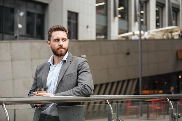 Imprenditore di successo uomo in abbigliamento formale che guarda da parte, in piedi e beve caffè da asporto davanti al moderno centro business