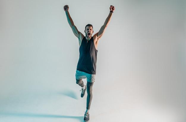 Sportivo europeo di successo che celebra la vittoria. giovane con la bocca aperta e alzando le mani. concetto di trionfo sportivo e vittoria. isolato su sfondo turchese. riprese in studio. copia spazio