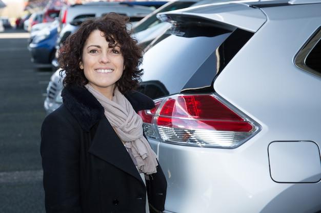Riuscito rappresentante di vendita femminile dell'automobile. commessa castana felice all'aperto.