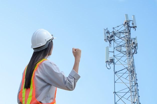 Ingegnere femminile di successo in piedi sullo sfondo della torre di comunicazione