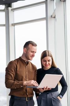 Un'impiegata di successo con una collega con un netbook si trova in un grattacielo sullo sfondo di una finestra che si affaccia sulla città. architetti della città che guardano il laptop soddisfatti del progetto