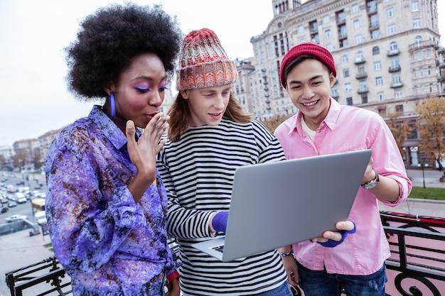 Liberi professionisti di successo. tre liberi professionisti abili astuti riusciti che esaminano insieme il computer portatile