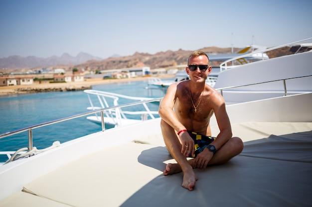 Un ragazzo di successo si siede su uno yacht bianco con vista sul mare. mar rosso, sole splendente