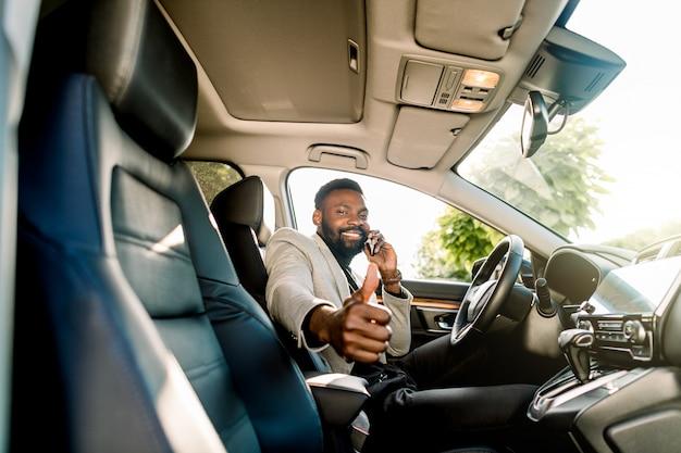 Riuscito uomo d'affari africano bello capo e capo seduto in macchina, parlando al telefono, sorridente, guardando la fotocamera e mostrando il pollice in su. concetto di affari