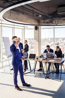 Un bell'uomo d'affari di successo in giacca e cravatta in ufficio con la sua squadra