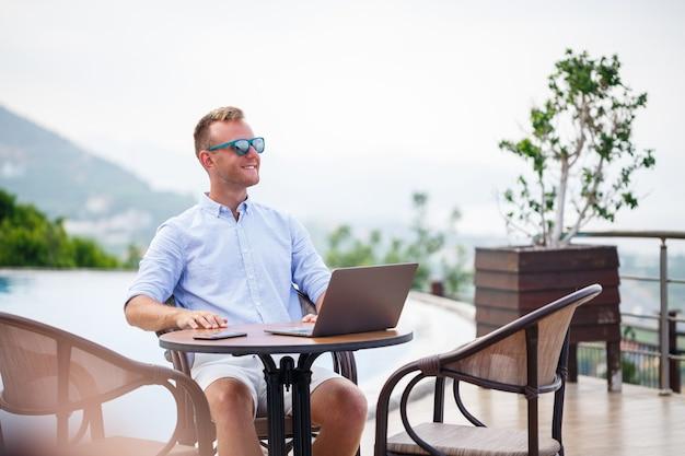 Un bell'uomo d'affari di successo in occhiali da sole lavora a un computer portatile seduto vicino alla piscina. lavoro a distanza. libero professionista