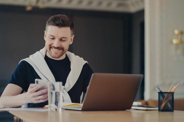 Libero professionista maschio bello di successo in abbigliamento casual che guarda lo smartphone e sorride mentre legge messaggi o buone notizie, seduto al suo posto di lavoro davanti al laptop a casa. business e concetto di lavoro