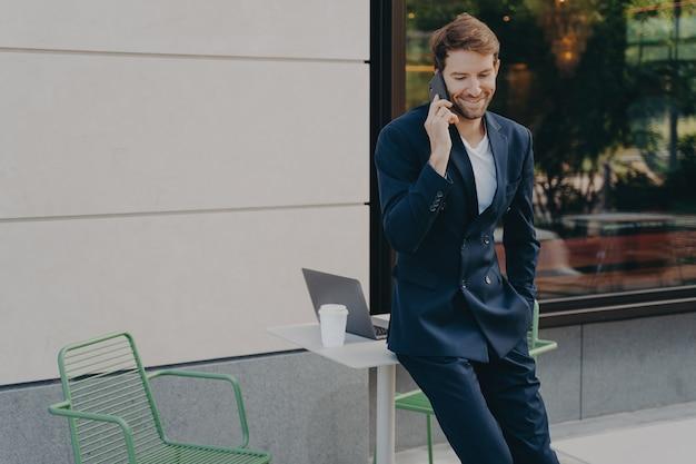 Commerciante maschio bello di successo che discute i prezzi delle azioni mentre si appoggia sul tavolo del caffè sul marciapiede
