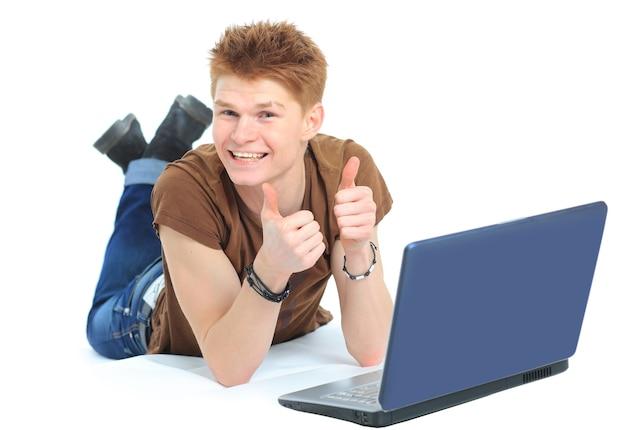 Uomo felice di successo sdraiato sul pavimento usando un laptop