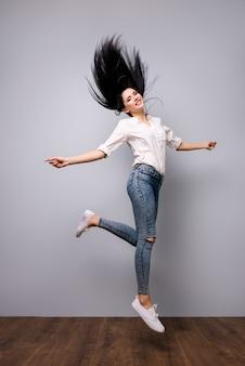 Riuscita donna graziosa felice isolata sullo spazio grigio che salta in su