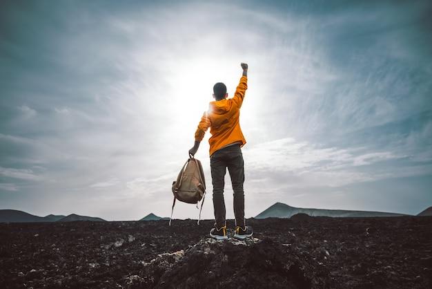 Escursionista di successo che fa un'escursione in montagna che punta al tramonto.
