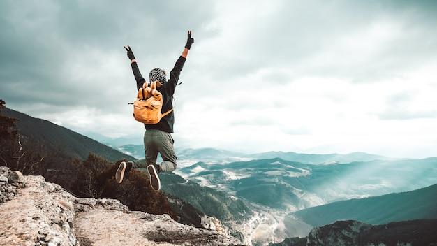 Uomo di escursionista di successo che salta sulla cima della montagna