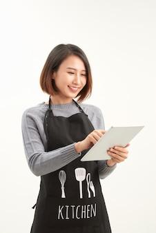 Impiegato di successo dell'ipermercato con il grembiule nero che tiene compressa moderna isolata su fondo bianco con copyspace