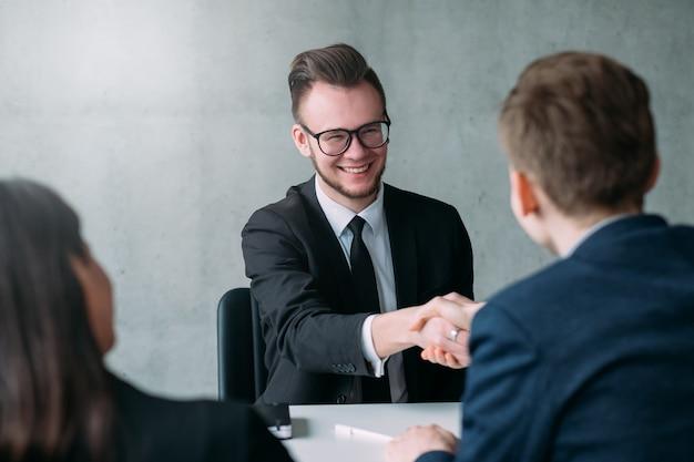 Colloquio di lavoro di successo. carriera professionale. risorse umane. il giovane candidato maschio è stato assunto per la posizione.