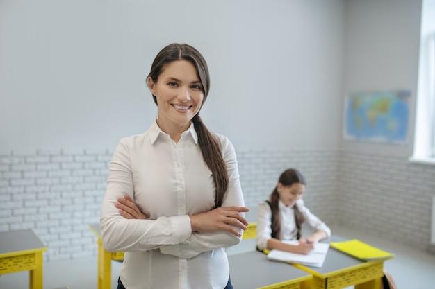 Insegnante di scuola gioiosa dai capelli lunghi di successo in aula durante la lezione e studentessa studiando alla scrivania
