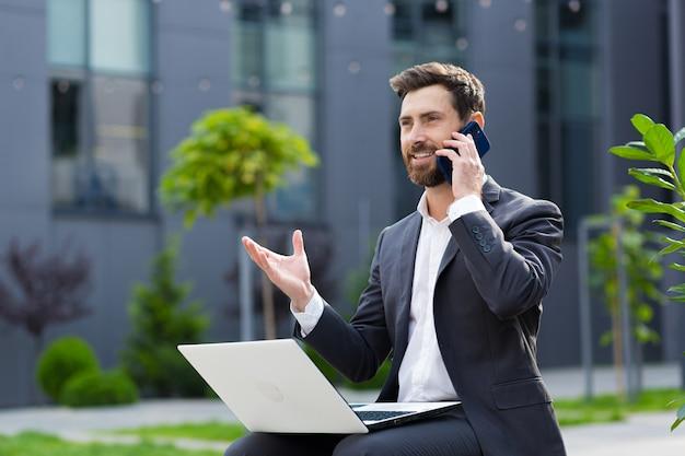 Un uomo d'affari di successo riporta buone notizie per telefono, lavorando con il laptop all'ora di pranzo vicino all'ufficio seduto sulla panchina