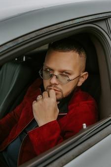 Uomo di successo alla guida di un'auto e con indosso occhiali scuri e un anello d'oro