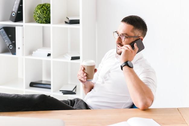 Uomo di successo in abbigliamento formale che parla su smartphone nero e beve caffè da asporto mentre è seduto in ufficio