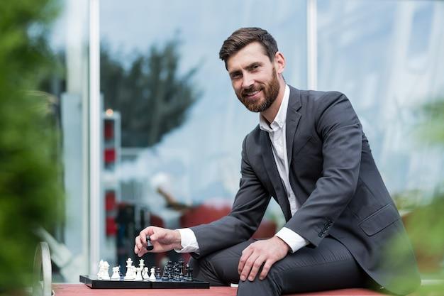Uomo di successo seduto su una panchina in giacca e cravatta che gioca a scacchi e guarda pensieroso la telecamera