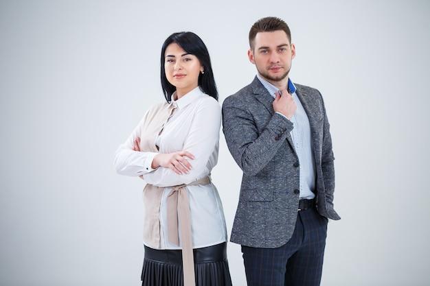 Un uomo di successo in giacca e una donna futuri uomini d'affari sorridono e parlano di un nuovo progetto. i partner commerciali stanno su uno sfondo bianco.