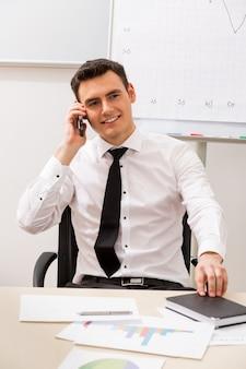 Il manager di successo conduce le conversazioni telefoniche addetto all'ufficio
