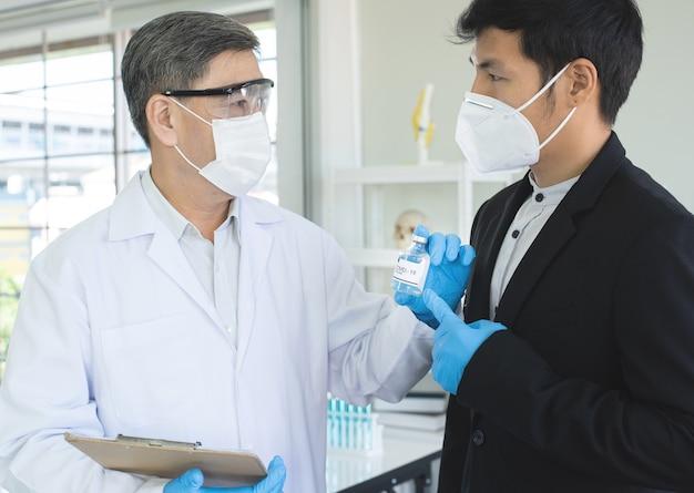 Ricercatore maschio maturo di successo o medico mostra il vaccino covid19 sull'invenzione di un nuovo vaccino a un uomo d'affari asiatico.
