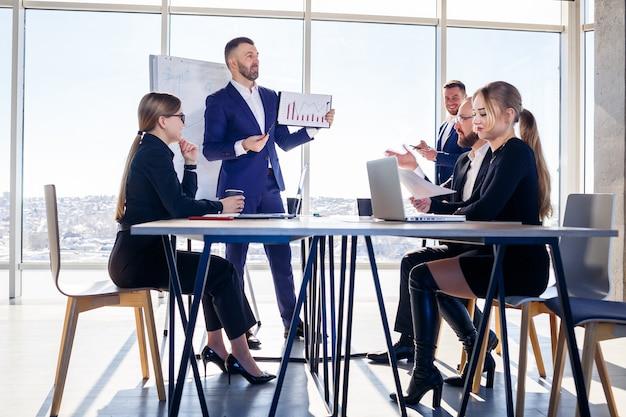 Riunione di successo di uomini d'affari, discussione di nuove idee imprenditoriali, utilizzo di diagrammi, seduta insieme. sfondo ufficio moderno. incontro di partner commerciali alla conferenza sullo sviluppo del business