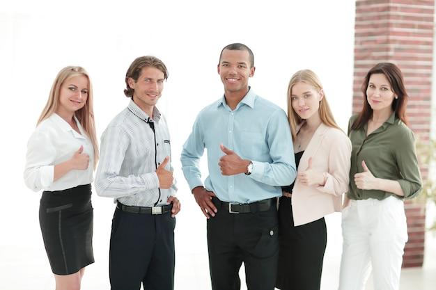 Riuscito team aziendale multinazionale che mostra pollice in su.il concetto di lavoro di squadra