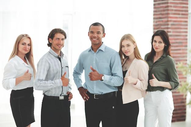 Team aziendale multinazionale di successo che mostra pollice in su
