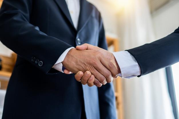 Il riuscito negoziato e il concetto della stretta di mano, due uomini d'affari stringono la mano con partner alla celebrazione la partnership e il lavoro di squadra, affare
