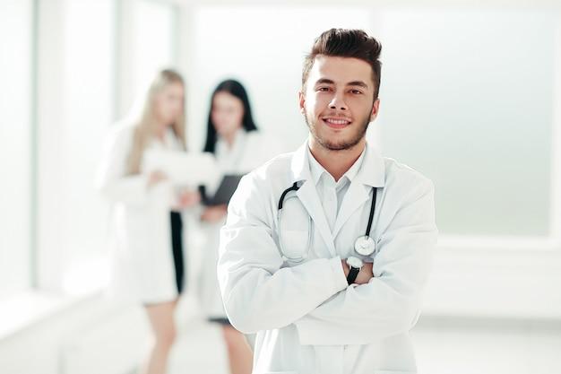 Pediatra di successo in piedi nel corridoio del centro medico