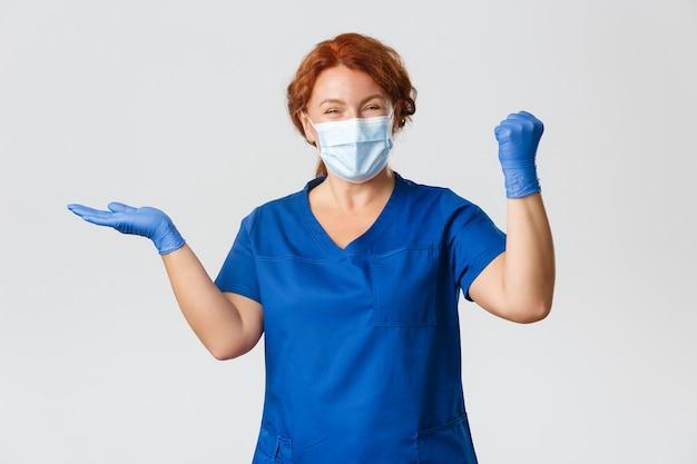 Dottoressa di successo e soddisfatta, felice, infermiera in maschera e guanti, tenendo in mano qualcosa e trionfante, pompa pugno allegra.