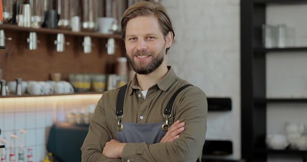 Uomo di successo del proprietario di piccola impresa che sta con le armi attraversate. ritratto di giovane proprietario maschio del caffè. concetto di caffetteria.