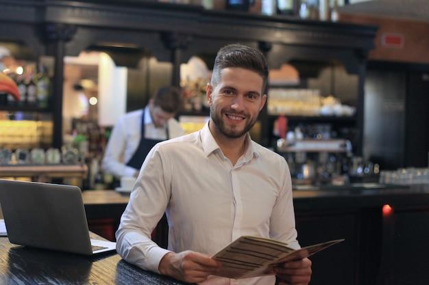 Piccolo imprenditore di successo in piedi con le braccia incrociate con un dipendente sullo sfondo che prepara il caffè.