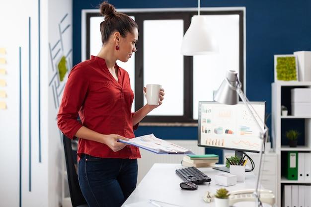 Donna d'affari concentrata focalizzata intelligente di successo che si gode una tazza di caffè