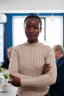 Donna d'affari africana sorridente di successo che tiene le braccia incrociate guardando la telecamera nella sala conferenze. manager che lavora in attività finanziarie di avvio professionale, luogo di lavoro aziendale moderno pronto per l'incontro