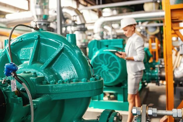 Gestore femminile sorridente riuscito laborioso in vestito che sta nella centrale termica con la compressa nelle mani e che controlla la turbina.
