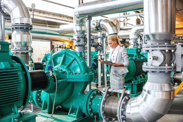 Gestore femminile sorridente riuscito laborioso in vestito che sta nella centrale termica con il ridurre in pani nelle mani e nel controllo sulla turbina